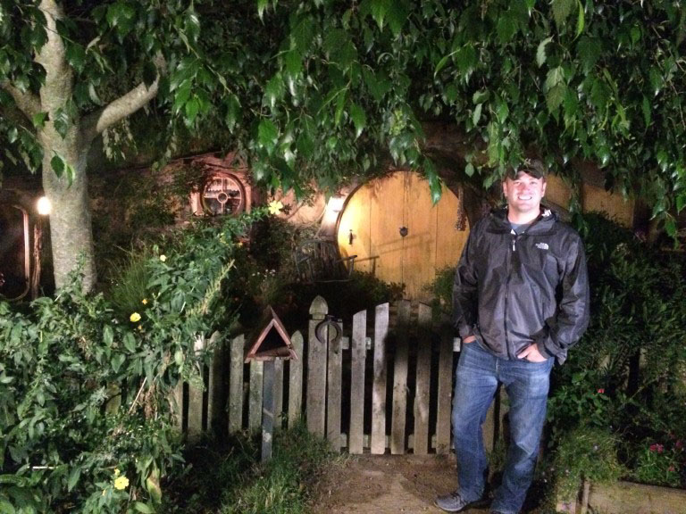 A tourist standing by a Hobbit Hole on the Hobbiton movie set