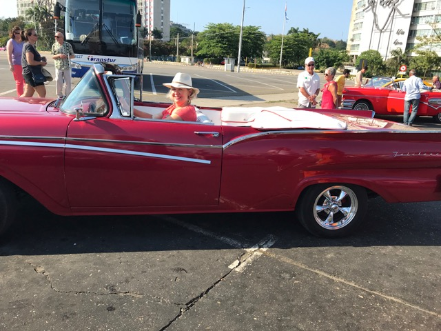 A woman in a red classic car in Cuba.
