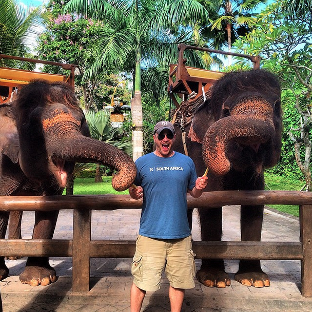 Lee Abbamonte in Bali with two elephants.