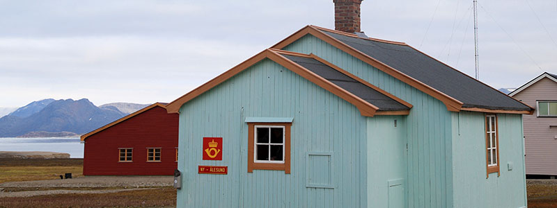 A squat blue building, known as the northernmost post office in the world, in Norway