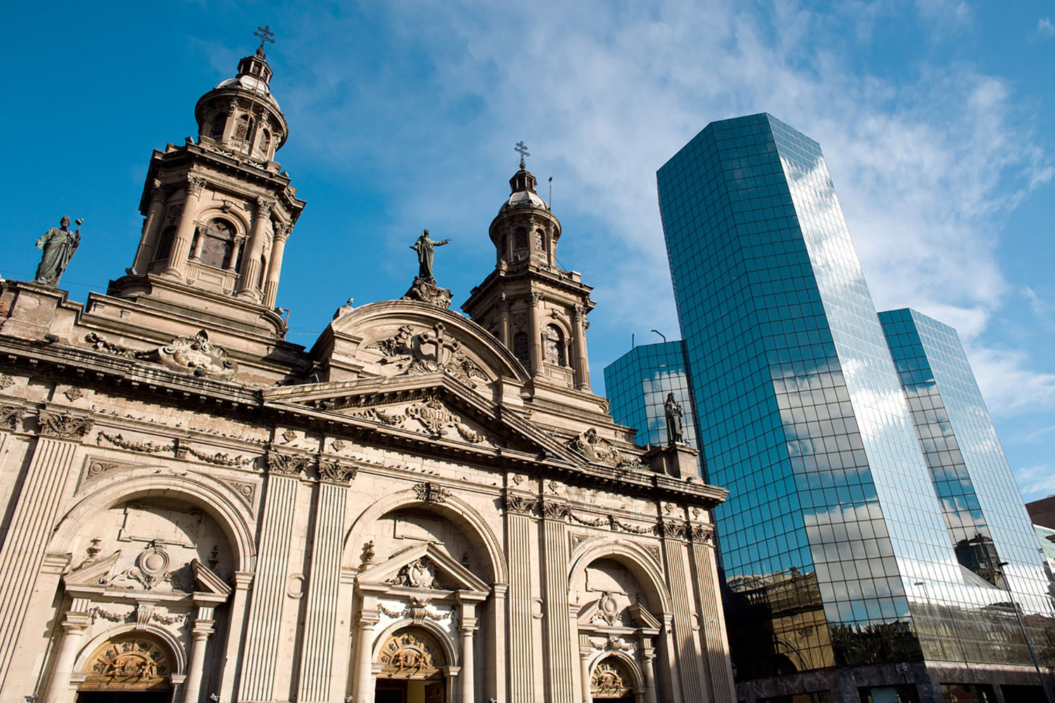 The Santiago Metropolitan Cathedral contrasted with a modern building in Santiago