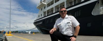 Captain Carl poses in front of the Azamara Quest cruise ship.