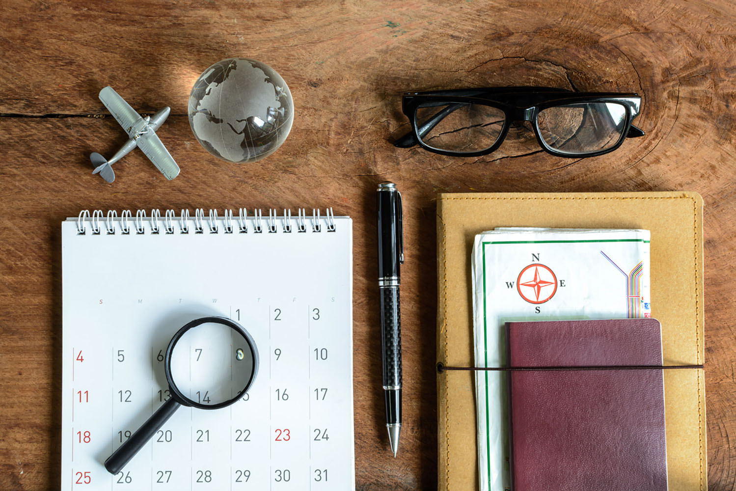 A travel calendar, glasses, a pen, and other important items for travel