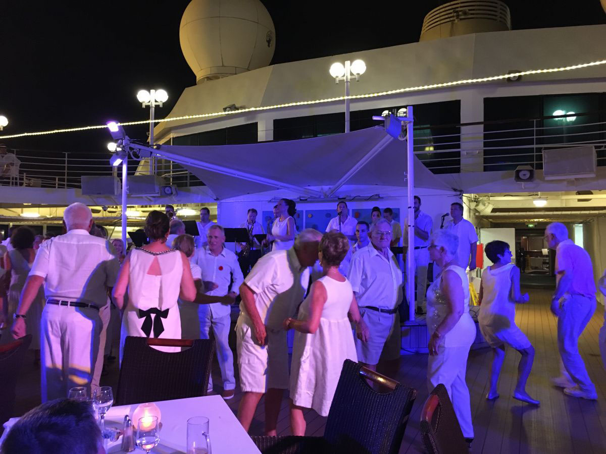 People dancing to the Azamara Quest Band on the deck of a cruise ship
